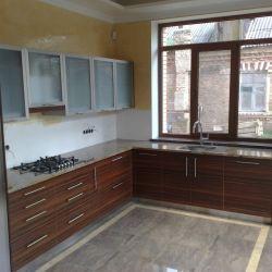 Кухонная столешница из бразильского гранита. На наш взгляд, очень красиво сочетается с фасадами под темное дерево