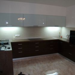Кухонная столешница из искусственного камня (кварцита) коричневого цвета. Вертикальная часть мебели также облицована этим кварцитом.