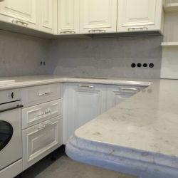 Кухонная столешница с фигурным фасоном из кварцита Caesarstone 5212. Рабочая поверхность (фартук) из того же материала.